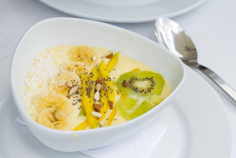 Iogurte com o quivi do chia da manga no prato cerâmico branco com toalhas de mesa brancas imagens de stock royalty free