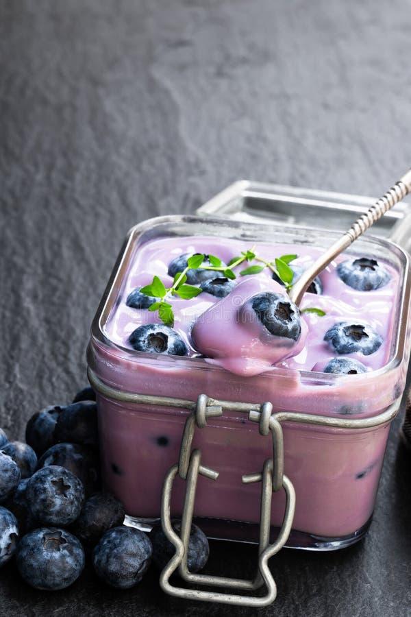 Iogurte de mirtilos fresco no frasco de vidro no fundo de pedra preto foto de stock royalty free