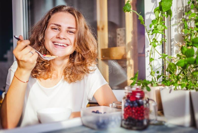 Iogurte de sorriso feliz bonito novo comer da mulher e berr fresco fotos de stock