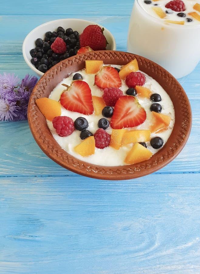 Iogurte do almoço da sobremesa do requeijão, morango da framboesa, abricó, mirtilo das bagas em um fundo azul fotografia de stock royalty free