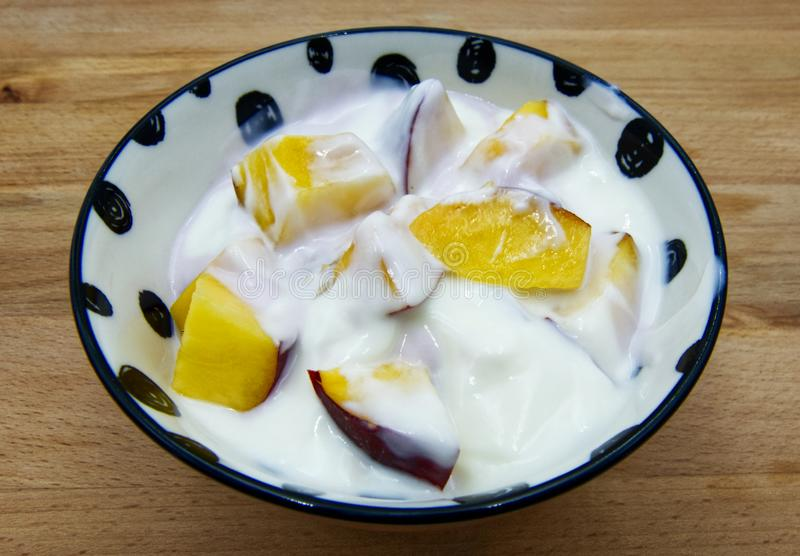 Iogurte em uma bacia com fatias do pêssego no fundo de madeira foto de stock royalty free