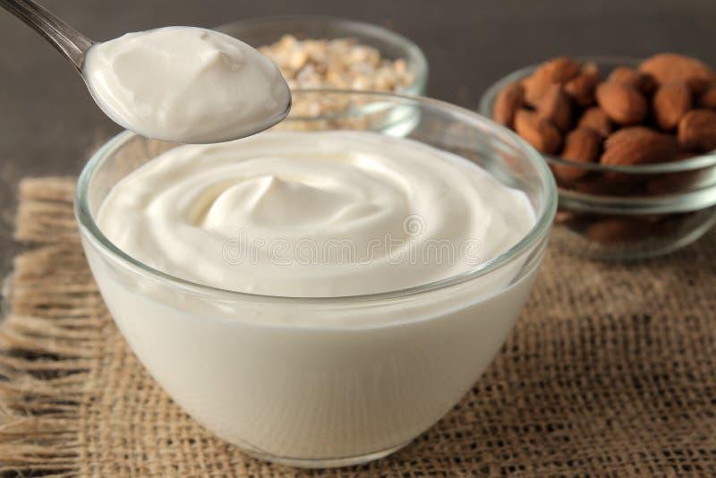 Iogurte grego em uma bacia de vidro ao lado de uma colher, de uma farinha de aveia e de umas amêndoas em um fundo escuro Alimento fotos de stock