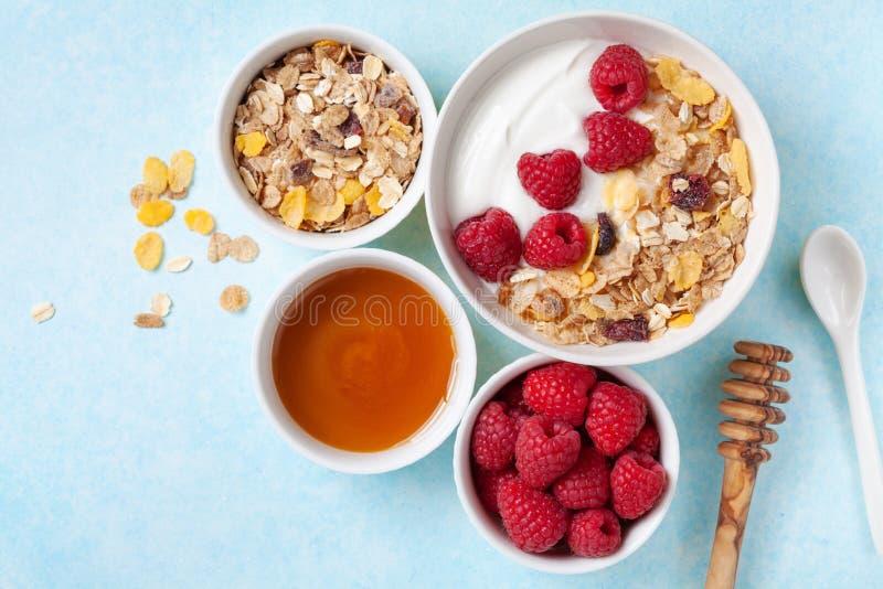 Iogurte grego na bacia com framboesas, mel e muesli dos ingredientes na opinião de tampo da mesa azul fotografia de stock royalty free