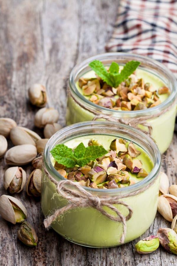 Iogurte natural do pistache em um frasco de vidro pequeno na tabela de madeira fotografia de stock royalty free