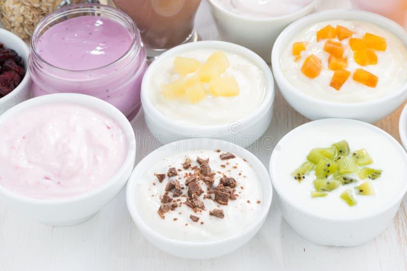 Iogurtes de fruto sortidos e ingredientes do café da manhã, close-up imagens de stock