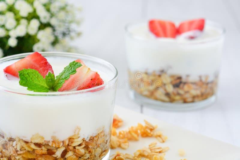Iogurtes de vidro com cereais e morangos, café da manhã fotografia de stock