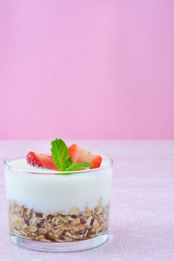 Iogurtes de vidro com cereais e morangos, fundo cor-de-rosa fotos de stock royalty free