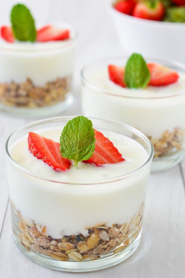 Iogurtes de vidro com cereais e morangos, madeira branca foto de stock