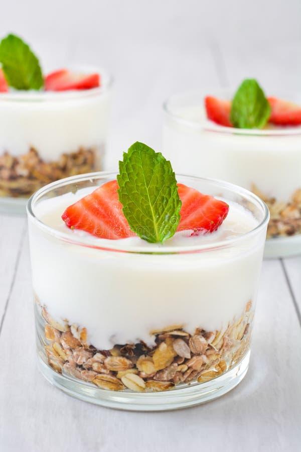 Iogurtes de vidro com cereais e morangos, madeira branca imagem de stock