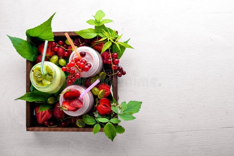 Iogurtes e listras da baga do fruto Em um fundo de madeira imagem de stock