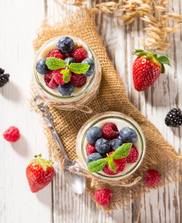 Iogurtes saborosos com muesli, as bagas frescas e o doce na tabela de madeira foto de stock royalty free