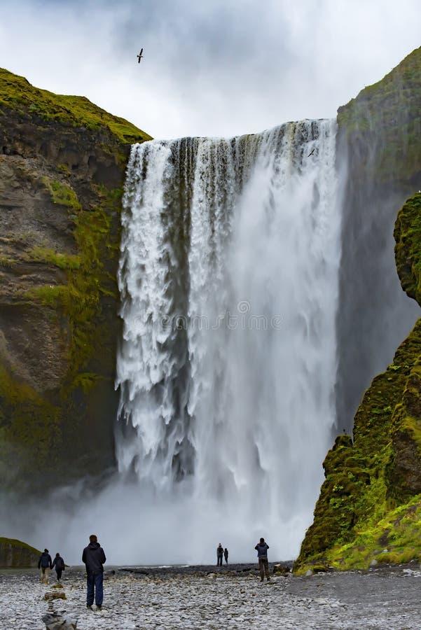 Ione Islanda della cascata di Skogafoss con alcune siluette dei touris fotografia stock