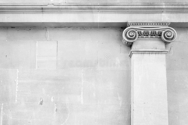 White false column capital over stone wall. The Ionic order forms, classical architecture background with white false column capital over stone wall. Bath stock images