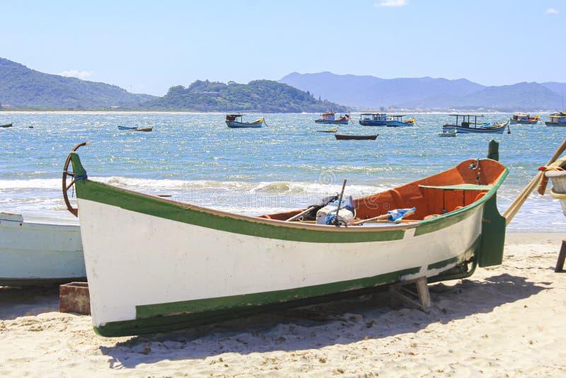 Ionische houten vissersboot op zeestrand met mooie lucht stock foto's
