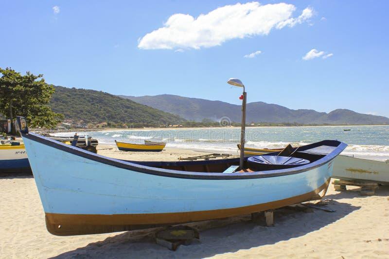 Ionische houten vissersboot op zeestrand met mooie lucht stock fotografie
