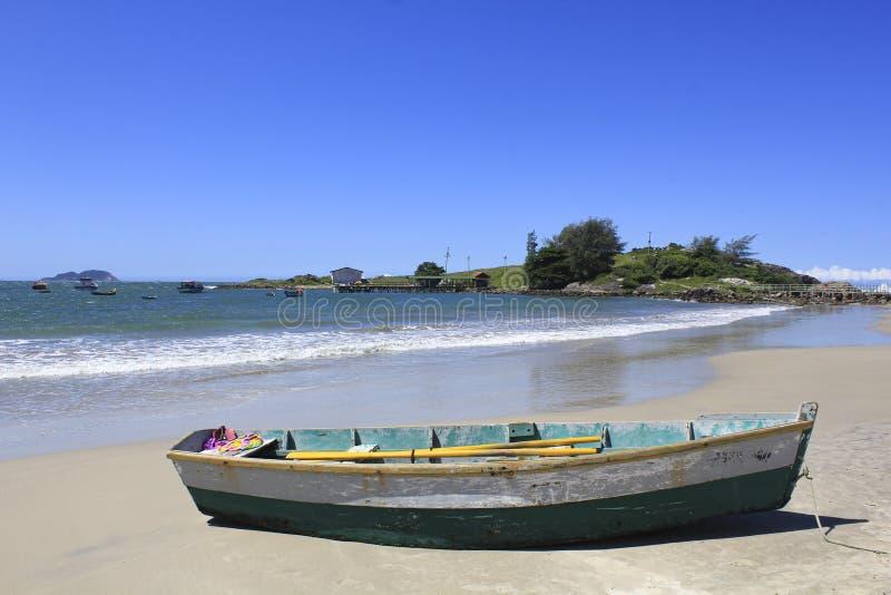 Ionische houten vissersboot op zeestrand met mooie lucht stock foto