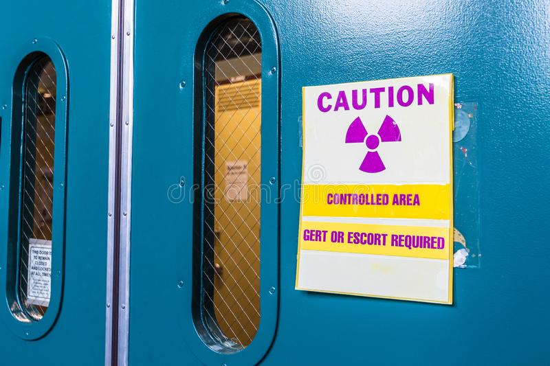 Ionizing radiation warning symbol displayed at the entrance to a laboratory; Message posted: stock image