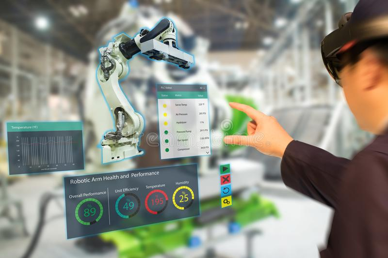 Iot industry 4.0 concept,industrial engineerblurred using smart glasses with augmented mixed with virtual reality technology to. Monitoring machine in real time stock photography