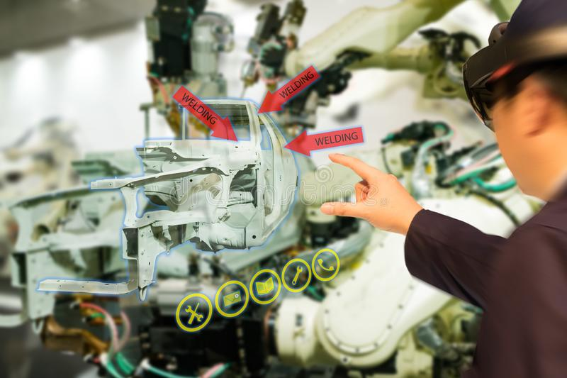 Iot industry 4.0 concept,industrial engineerblurred using smart glasses with augmented mixed with virtual reality technology to. Monitoring machine in real time stock images