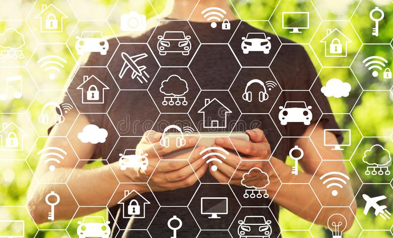IoT theme with man holding his smartphone stock image