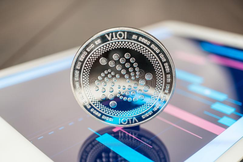 Close-up photo of iota cryptocurrency physical coin on the tablet computer showing stock market charts. trading iota cryptocoin stock photography