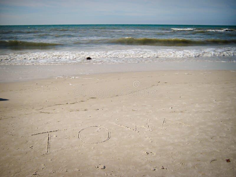 Iowa written in sand. The word IOWA written in the sand, on a warm, beautiful beach in Florida stock photography