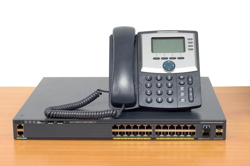 IP phone and networking switch on wood table royalty free stock photography