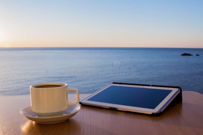Ipad blanco de la tableta en el escritorio de la tabla con la taza de café, con paisaje del mar fotografía de archivo