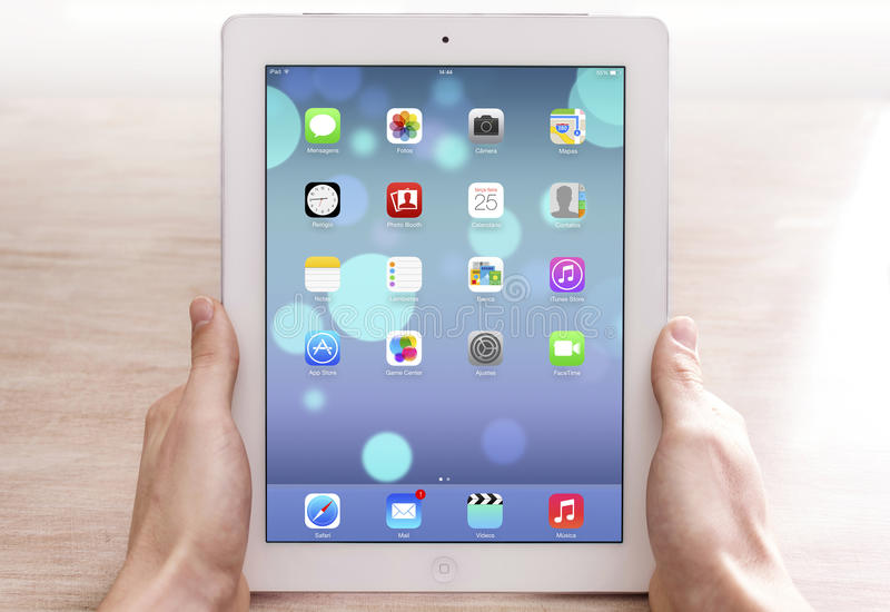 Ipad on hand. Man's hands holding an Apple new ipad with new ios 7 operating system stock images