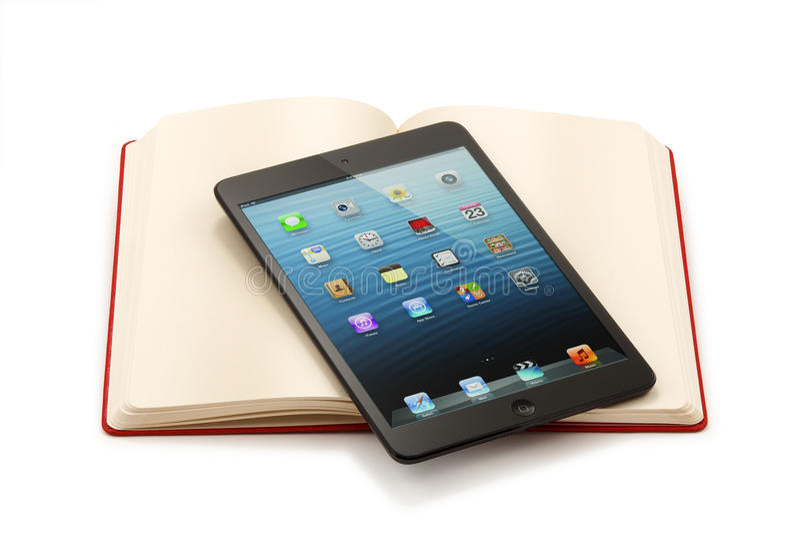Ipad Mini auf offenem Buch - Beschneidungspfad stockbild