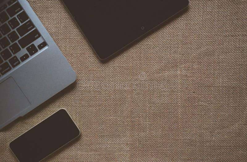 Ipad noir près du Macbook sur le textile brun image stock