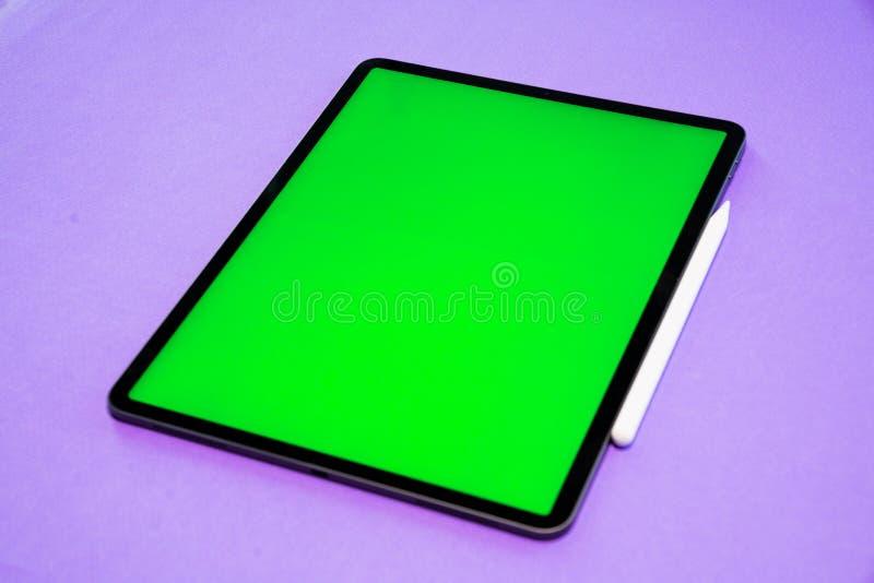 IPad und iPhone, neue Tablette auf einem violetten Hintergrund mit einem Stift und Draufsicht des grünen Schirmes stockfotografie