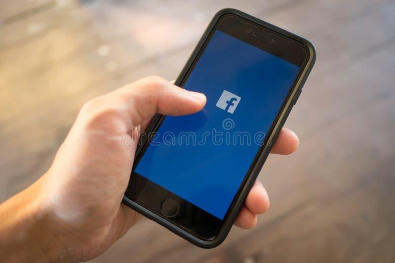 IPhone 7 in één hand wordt gehouden die het zijn scherm met Facebook-embleem tonen dat stock afbeelding