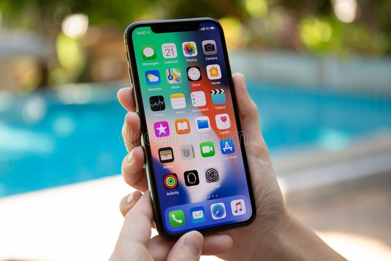 IPhone Χ εκμετάλλευσης χεριών γυναικών με IOS 11 στην οθόνη στοκ φωτογραφίες