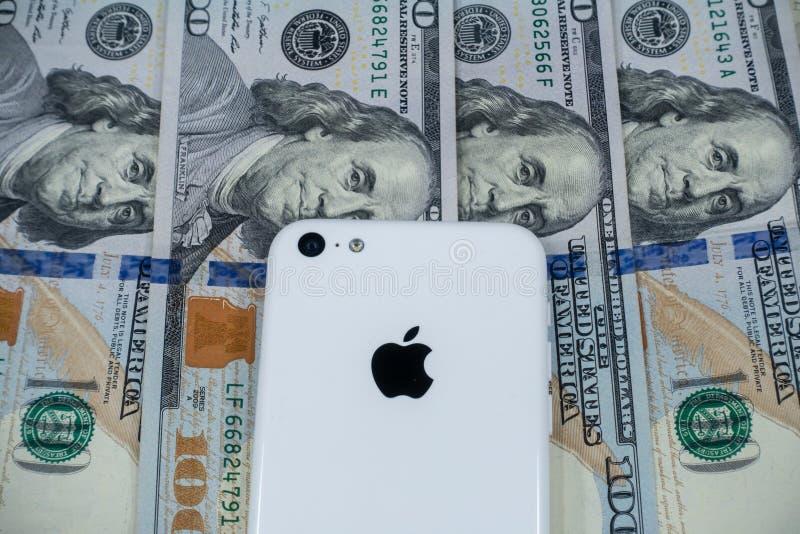 Iphone Яблока и стратегически установленный $100 счетам стоковая фотография