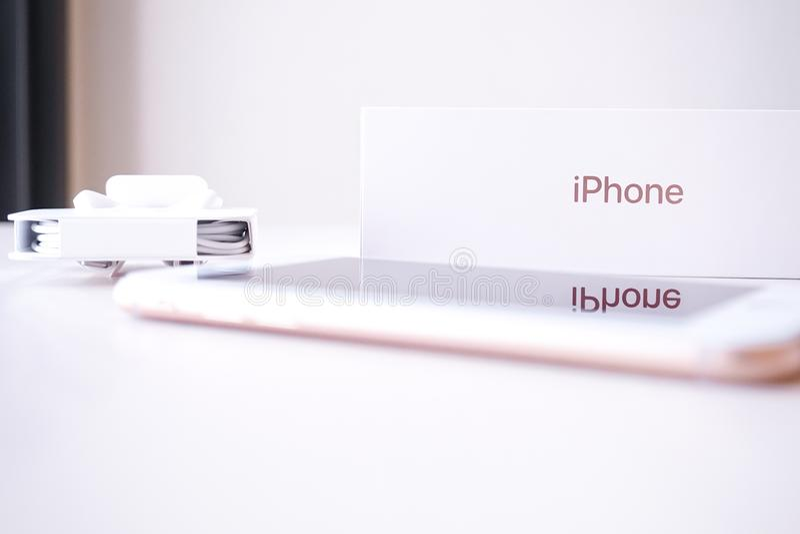 IPhone8罗斯金子在与包装的桌上在背景 图库摄影