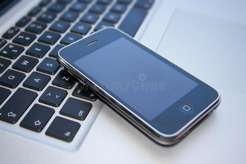 IPhone 3GS and Macbook Pro. IPhone 3GS on top of a Macbook Pro stock photo