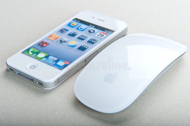 iPhone blanco 4 (S) y ratón mágico imagenes de archivo