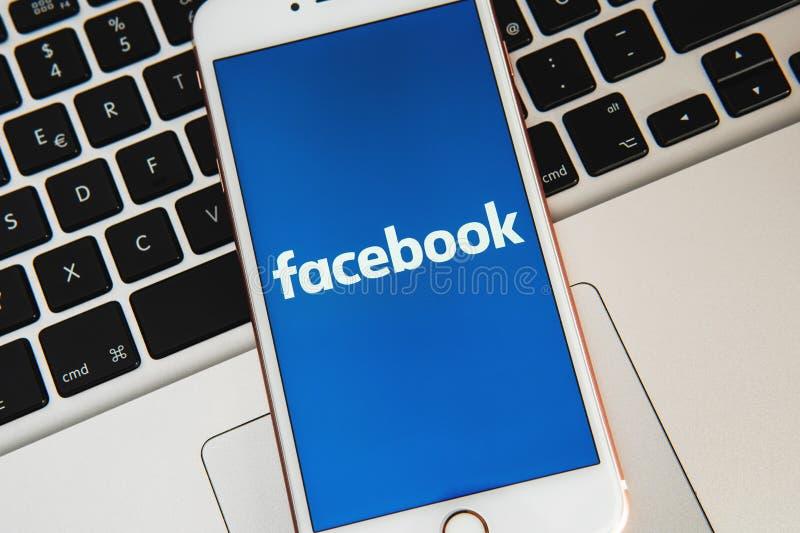 IPhone blanco con el logotipo de los medios sociales Facebook en la pantalla foto de archivo
