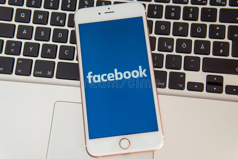 IPhone blanco con el logotipo de los medios sociales Facebook en la pantalla imagen de archivo libre de regalías