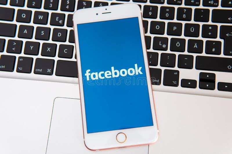 IPhone blanco con el logotipo de los medios sociales Facebook en la pantalla fotos de archivo libres de regalías
