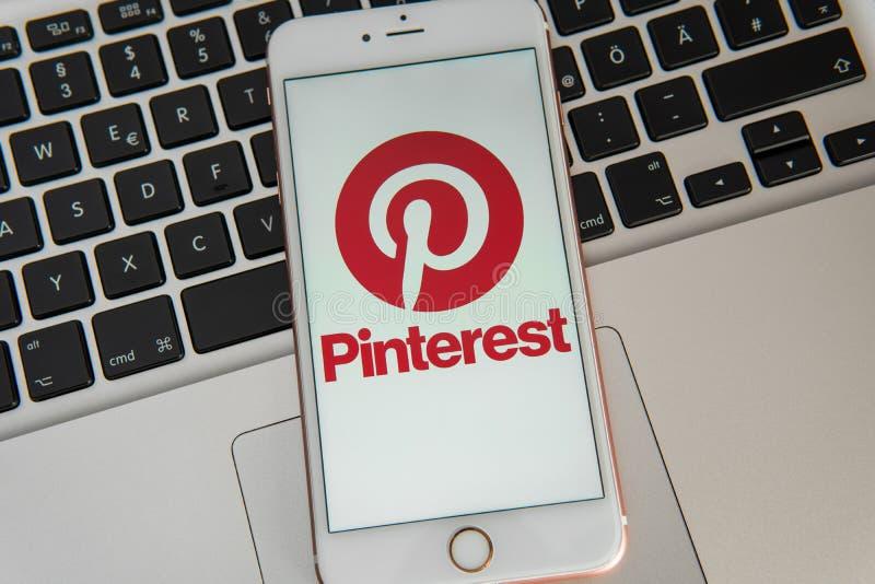 IPhone blanco con el logotipo de los medios sociales Pinterest en la pantalla imagen de archivo libre de regalías