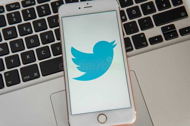IPhone blanco con el logotipo de los medios sociales Twitter en la pantalla imagenes de archivo