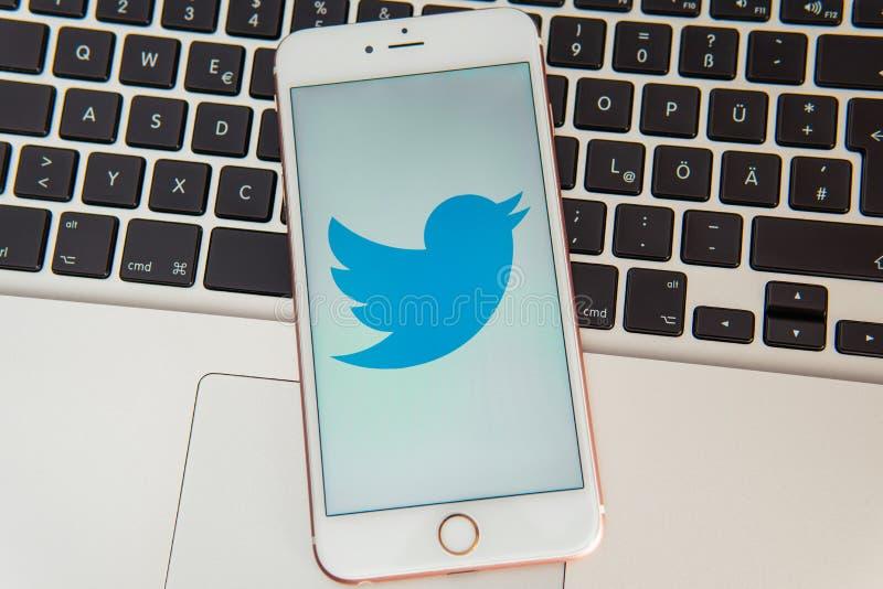 IPhone blanco con el logotipo de los medios sociales Twitter en la pantalla foto de archivo