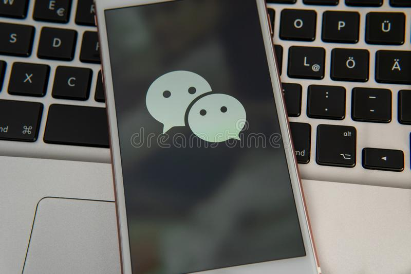 IPhone blanco con el logotipo de los medios sociales WeChat en la pantalla fotografía de archivo