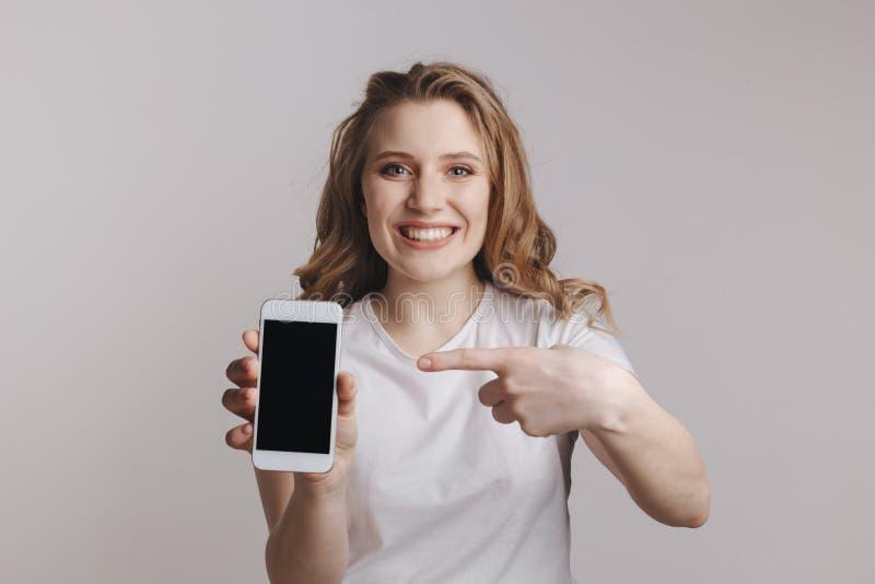 Iphone branco da terra arrendada da jovem mulher de Handsopme isolado sobre o fundo branco fotografia de stock