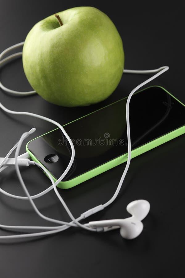 IPhone 5C z EarPods i zielonym jabłkiem fotografia stock
