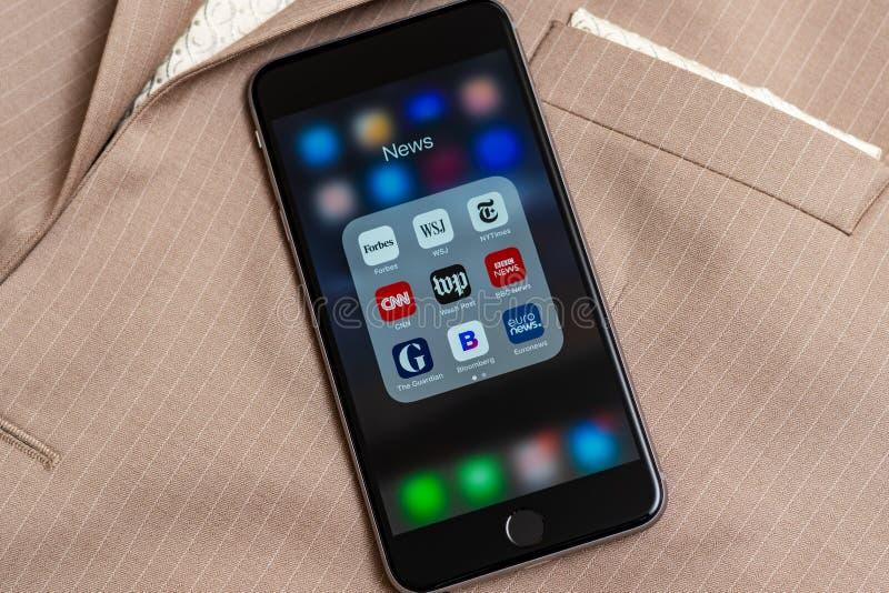 IPhone con los iconos de los medios de noticias: Usos de Forbes, de WSJ, del NY Times, de CNN, del WP, del BBC News, del guarda,  foto de archivo libre de regalías