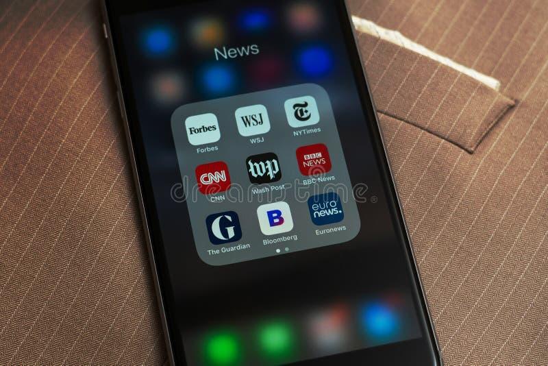 IPhone con los iconos de los medios de noticias: Usos de Forbes, de WSJ, del NY Times, de CNN, del WP, del BBC News, del guarda,  imagen de archivo libre de regalías