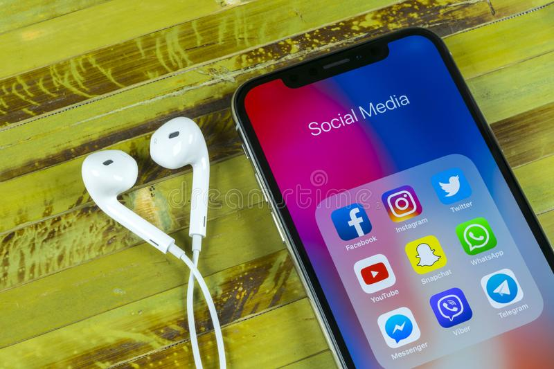 IPhone X de Apple com ícones do facebook social dos meios, instagram, gorjeio, aplicação do snapchat na tela Ícones sociais dos m